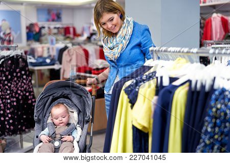 Young Stylish Woman In Blue Jacket And With Baby In Stroller Choosing Dress In Clothing Store