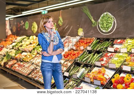 Young Stylish Woman In Blue Jacket Staying Confused In Front Of Vegetables Stand In Grocery Store