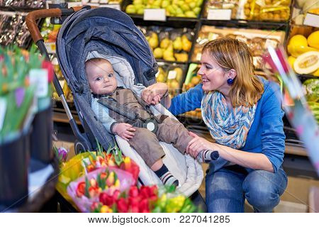 Young Woman Smiling To Her Baby Son In Grocery Store