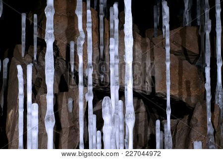 Thin High Icy Columns In A Cave On The Background Of Brown Stones