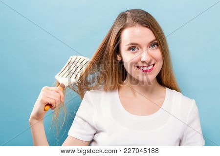 Beautiful Woman Holding A Hairbrush On Blue Background