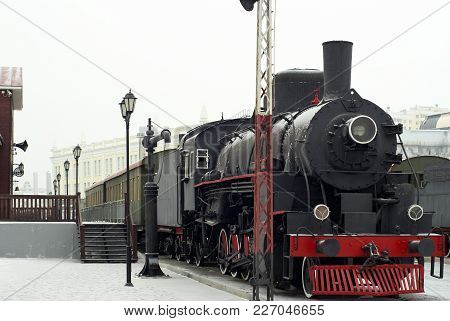 Vintage Steam Locomotive With Wagons Standing At The Railway Station In Winter