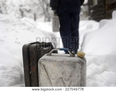 Two Petrol Cans In The Foreground And A Man With With Jerry Can In The Blurred Background