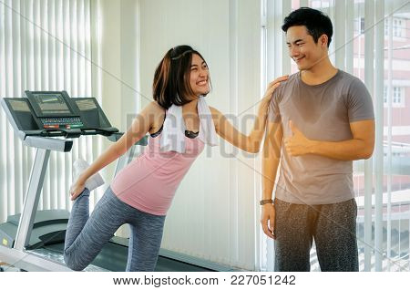 Asian Young Smiling Sport Woman Stretching In Fitness Gym Center With Personal Trainer Man Showing T