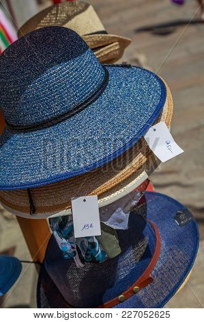 Several Straw Hat Stacked In Front Of A Merchant Shop On Sunny Day