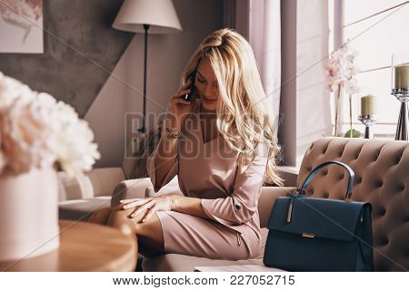 So Good To Hear You. Attractive Young Woman In Elegant Dress Talking On Smart Phone And Smiling Whil