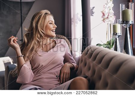 Modern Female. Attractive Young Woman In Elegant Dress Keeping Hand In Hair And Smiling While Sittin