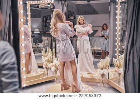 Amazing Dress.  Full Length Of Attractive Young Women Trying On Wedding Dress While Spending Time In