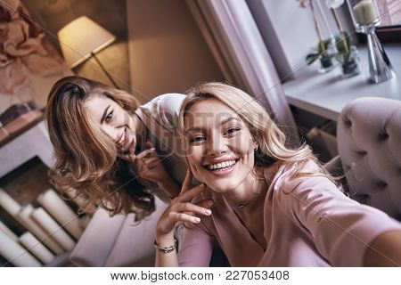 Flirty Beauties.  Top View Self Portrait Of Attractive Young Women Smiling And Looking At Camera Whi
