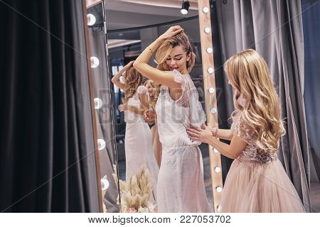 Great Look! Young Beautiful Woman Adjusting A Dress On Her Girlfriend While Standing In The Fitting