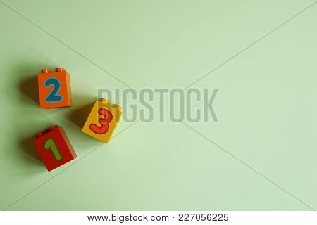 Colorful Plastic Bricks With Numbers On Light Green Background. Educational Toys. Top View Image Wit
