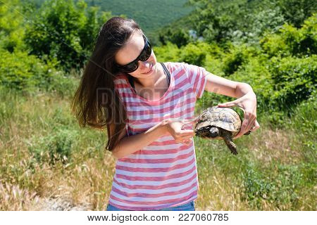 Close-up Woman Brunette In Sunglasses And Striped T-shirt Keeping Turtle In Her Hands In The Forest.