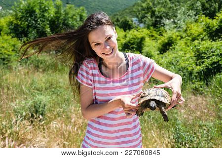 Close-up Woman Brunette In Striped T-shirt And Jeans Shirt Keeping Turtle In Her Hands In The Forest