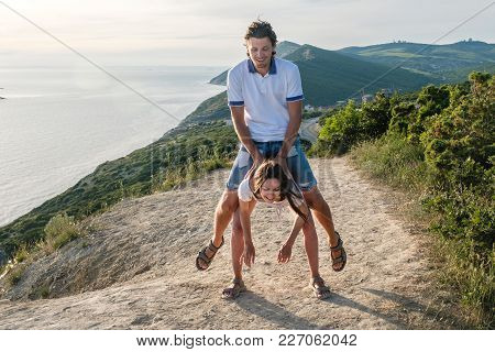 Woman Lifts Man. Fun Pastime On The Mountain With Seascape