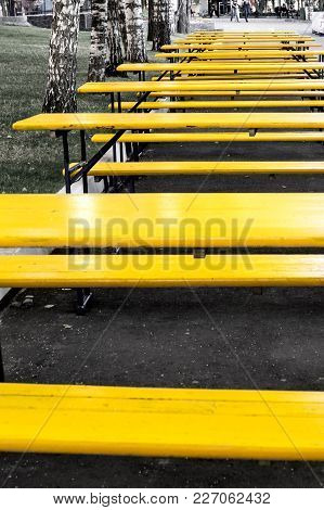 Set Of The Wooden Yellow Tables Standing Outdoor