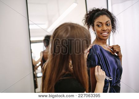 Fashion Designer Designing Clothes In Her Fashion Studio Along With A Model