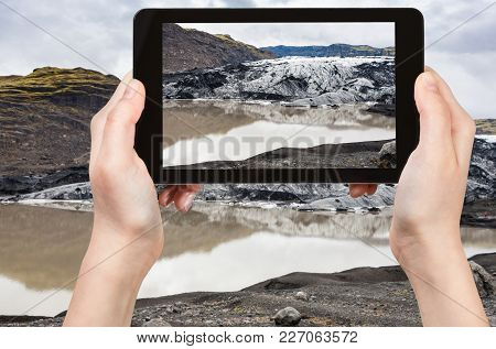 Travel Concept - Tourist Photographs Melting Water And Solheimajokull Glacier (south Glacial Tongue