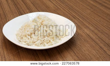 Semi Milled Rice In White Plastic Plate On Wood Ready To Eat And Has Copy Space.