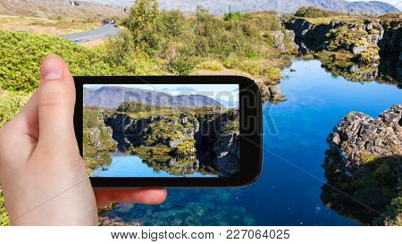Travel Concept - Tourist Photographs Silfra Fissure In Rift Valley Of Thingvellir National Park In I