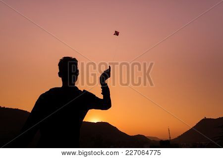 Young Boy Playing With Kite At Sunset. Backlight, Colorful Sky, Rear View, Rajasthan, India.