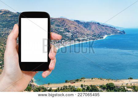 Travel Concept - Tourist Photographs Letojanni Resort Town On Beach Of Ionian Sea Near Taormina City