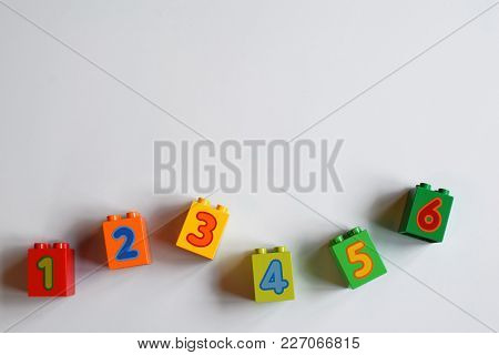 Colorful Plastic Bricks With Numbers On Very Light Blue Background. Educational Toys. Top View Image