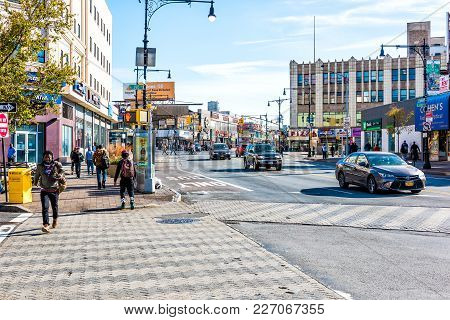 Bronx, USA - October 28, 2017: People crossing street in Fordham Heights center, New York City, NYC morning, cars, sunny day