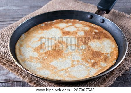 Frying Pan With Tasty Thin Pancakes On Table