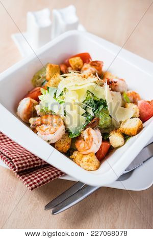 Classic Caesar Salad With Shrimps In A White Plate On A Wooden Table, Selective Focus