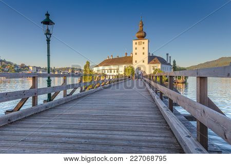 Beautiful View Of Famous Schloss Ort With Wooden Bridge At Lake Traunsee In Beautiful Golden Evening