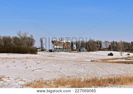 An Abandoned Barn And Farmstead In A Grove After A Snowfall