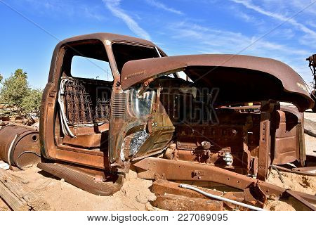 A Side Profile Of A Very Old Rusting Truck Missing The Door And An Open Hood Exposing The Engine,