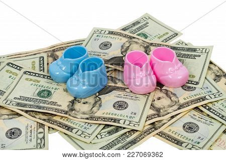 A Horizontal Shot Of A Pair Of Blue And Pink Plastic Baby Booties Sitting On A Pile Of Twenty Dollar
