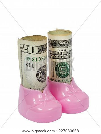 Vertical Shot Of A Pair Of Pink Plastic Baby Booties Filled With Rolls Of Bills On A White Backgroun