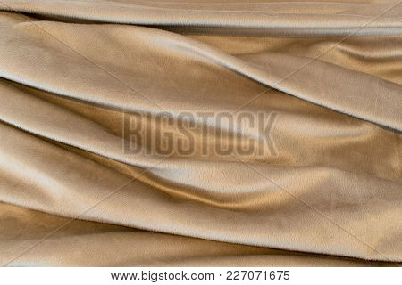 Beige Blanket Arranged In Such A Way As To Show Deep Folds That Are Horizontal.
