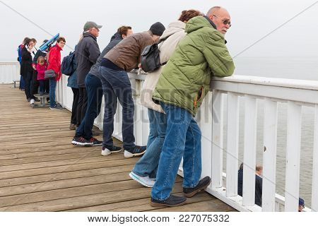 Cuxhaven, Germany - May 19, 2017: People At Wooden Pier Of Cuxhaven Waiting For Ferry To German Isla