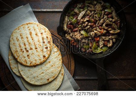 Tortilla On Parchment And Frying Pan With Filling Horizontal