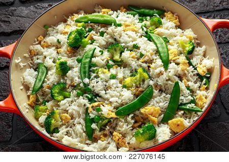 Fried Rice With Vegetables, Broccoli, Peas And Eggs Served In A Pan. Healthy Food.
