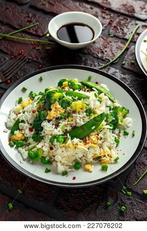 Fried Rice With Vegetables, Broccoli, Peas And Eggs In A Plate. Soy Sauce. Healthy Food.