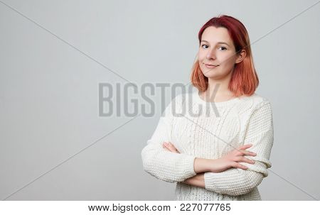 Portrait Of Young Pretty Positive Girl In A White Sweater, Smiling Looking At Camera With Crossed Ar