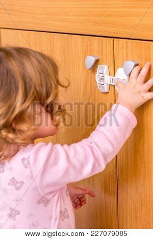 Baby Girl Trying To Open The Kitchen Cabinet - Baby Proofing The Door