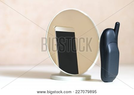 The Outdated Model Of A Cell Phone Located On A White Background In Front Of The Mirror Sees In The