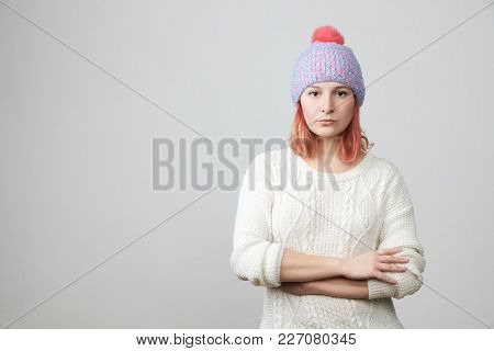Portrait Of Offended Unhappy Beautiful Woman In Knitted Hat, Keeps Hands Crossed, Curves Lips, Displ