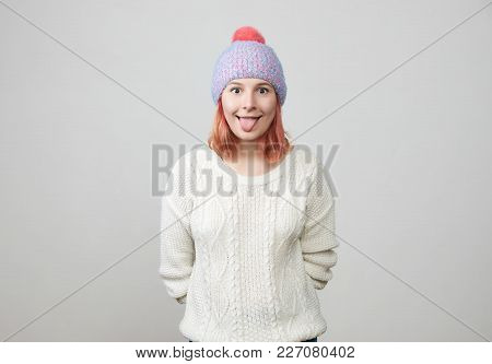 Funny Pretty Girl In Hat, Sticking Out Her Tongue. Young Female Mocking While Having Fun Indoors. Pe