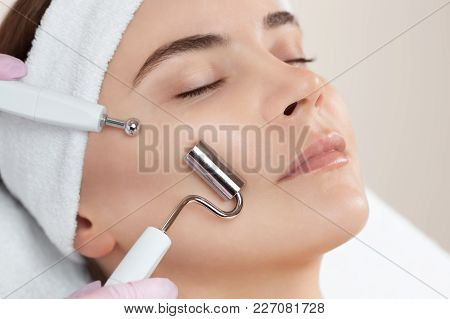 The Cosmetologist Makes The Apparatus A Procedure Of Microcurrent Therapy Of A Beautiful, Young Woma