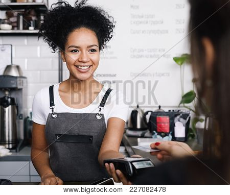 Smiling Cashier Accepting Payment Over Nfc Technology, Looking On A Buyer