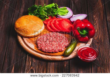 Raw Ground Beef Meat Burger Steak Cutlets With Seasoning, Cheese, Tomatoes, Salad And Bun On Vintage