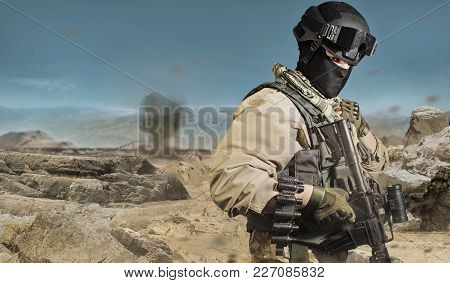 Photo Of A Fully Equipped Military Soldier Standing With Rifle, Ammo On Desert Battlefield Backgroun