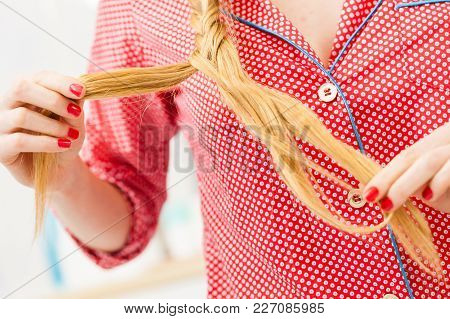 Fancy Trendy Blond Hairstyle At Home Concept. Closeup Of Woman Doing Braid On Blonde Hair