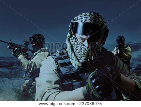 Special Operation Military Soldiers Posing On Night Desert Background.
